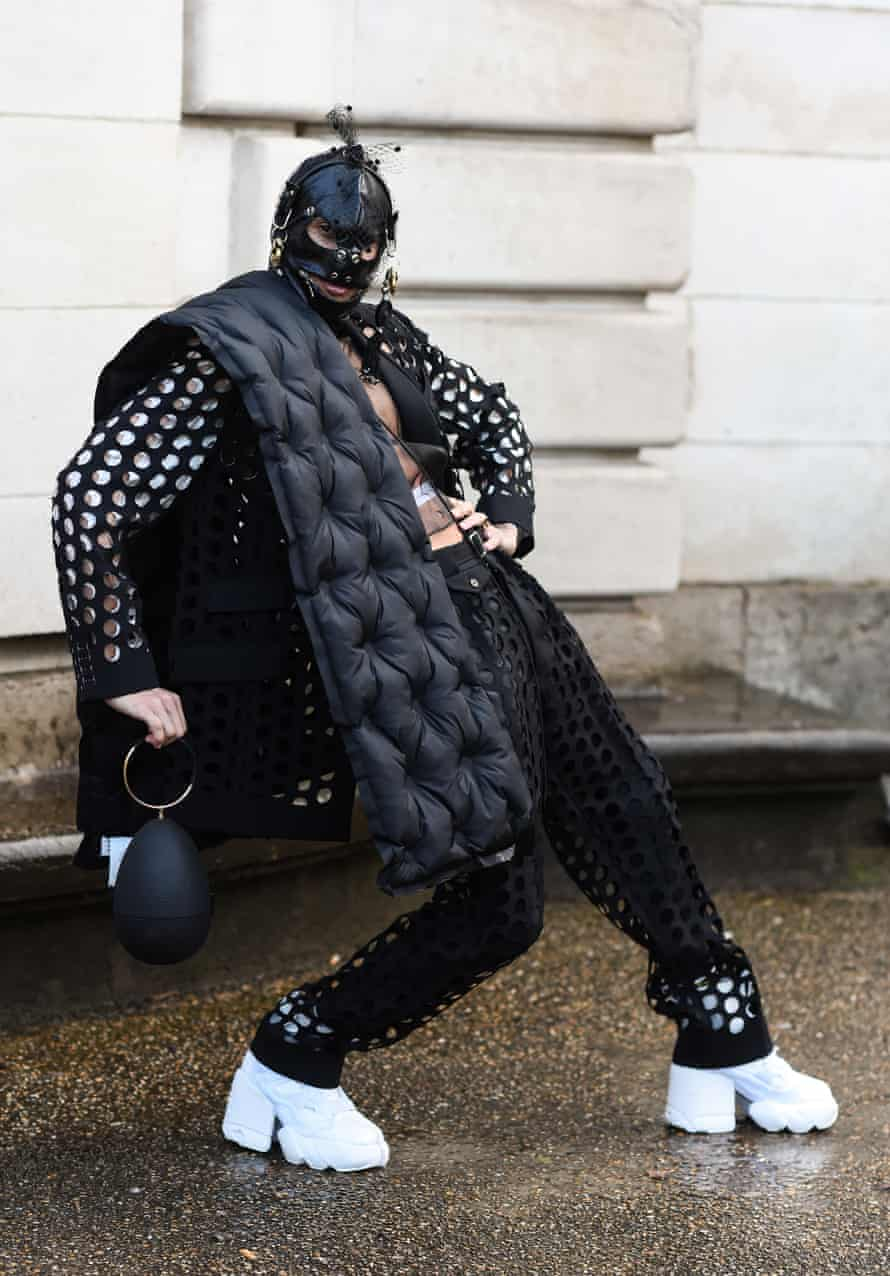A guest in a Maison Margiela outfit and leather mask.