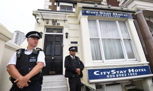 Police stand guard outside the City Stay hotel in east London where the Russian suspects are said to have stayed.
