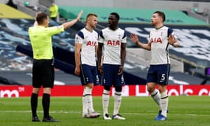 Tottenham players surround referee Peter Bankes after he awards a penalty against Eric Dier.