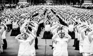 Thailand celebrates the King's Birthday. Hundreds of local school children are executing a choreographed and synchronised meditation towards their head of state.