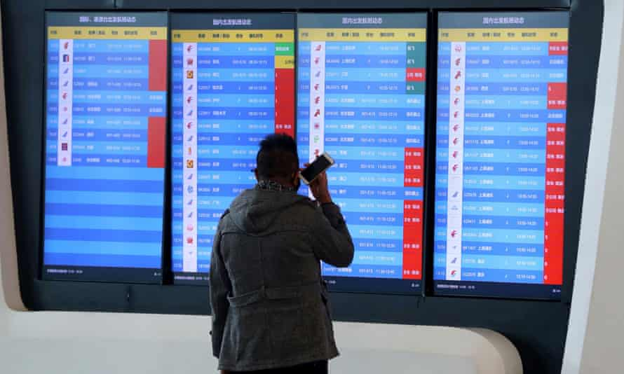 A man stands in front of a screen showing cancelled flights at the airport in Wuhan