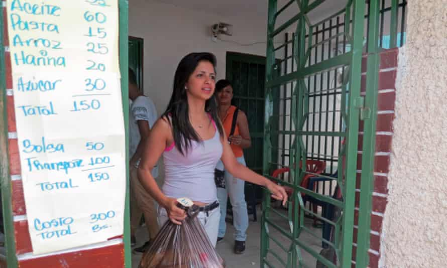 A resident of the Carapita neighbourhood of Caracas walks away with a bag of basic goods she bought for 300 bolivars (70 cents).