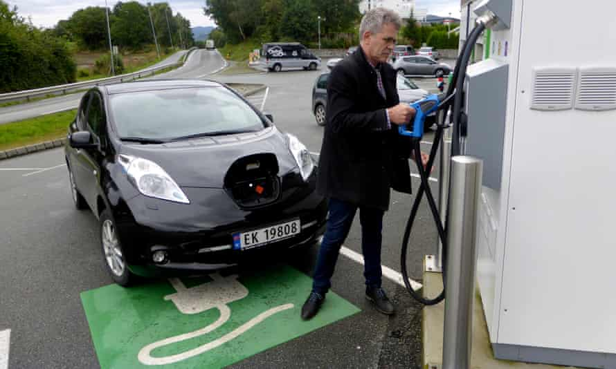 A man recharges his Nissan Leaf electric car in Norway.