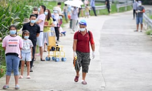 A worker sprays disinfectant as villagers wait in a line for nucleic acid testing at Boyangping village during a citywide COVID-19 testing campaign on 12 August.