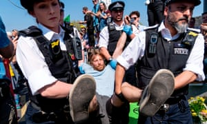 Police officers break up the Extinction Rebellion demonstration blocking Waterloo Bridge in London.