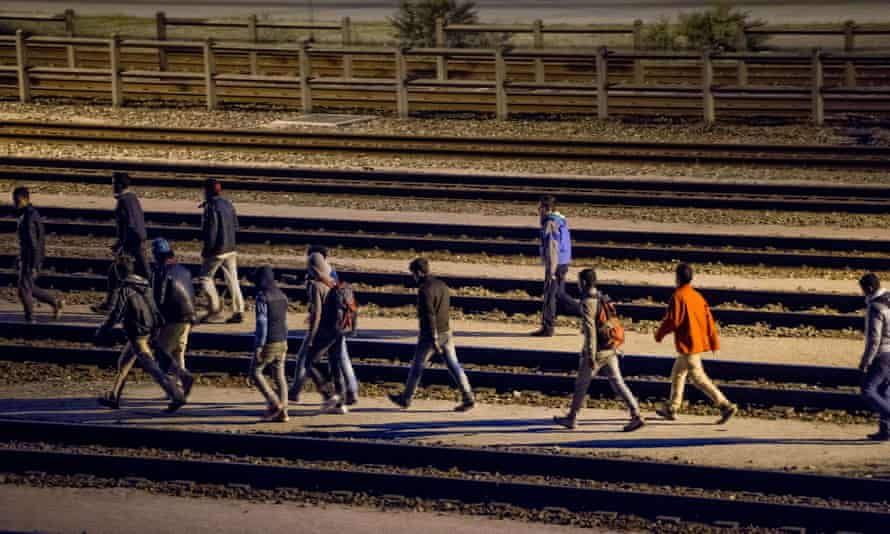 Migrants walk along railway tracks at the Eurotunnel terminal on 28 July.