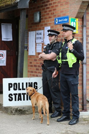 Police officers keep an eye on a voter's dog as they wait outside the polling station where the Conservative party leader, Theresa May, is expected to vote in Maidenhead