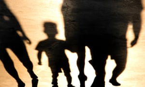 Blurry shadow of a small boy and adults walking in sunset