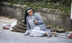 A nun checks her mobile phone as she lies near an earthquake victim in Amatrice.