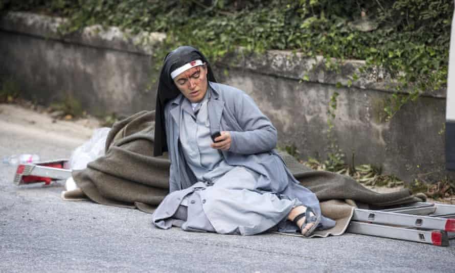A nun checks her mobile phone as she lies near an earthquake victim in Amatrice.