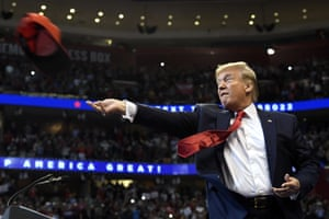 President Donald Trump throws a cap as he arrives to speak at a campaign rally in Sunrise, Florida