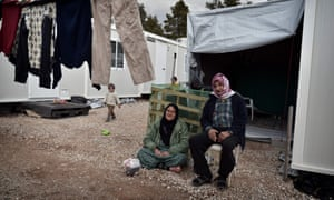People sit near their container home in the Ritsona refugee camp, north of Athens, in December.