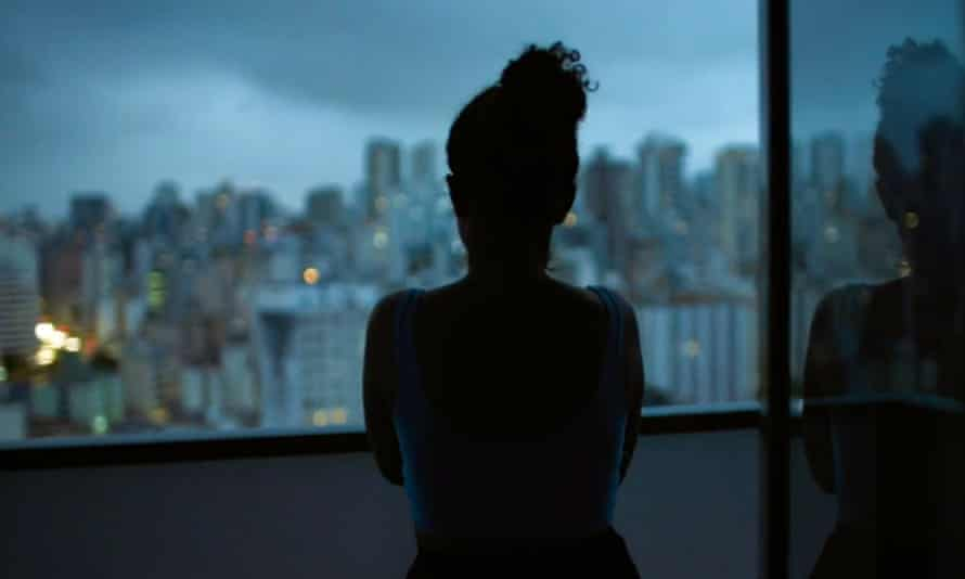 Silhouette of a woman looking out of an apartment window