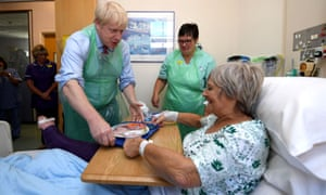 Boris Johnson serves food to Wenona Pappin, aged 70, during a visit to Torbay Hospital in Torquay,