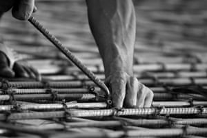 Metal Hand by David Bajrai, Assam, India<br> A metal rod is a main component for the process of building. In this picture the man is joining these rods together to make a metal coil.