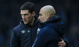 Huddersfield's caretaker manager Mark Hudson talks to Pep Guardiola at the final whistle.