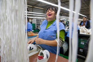 A woman laughs as she laces up a completed pair of shoes.