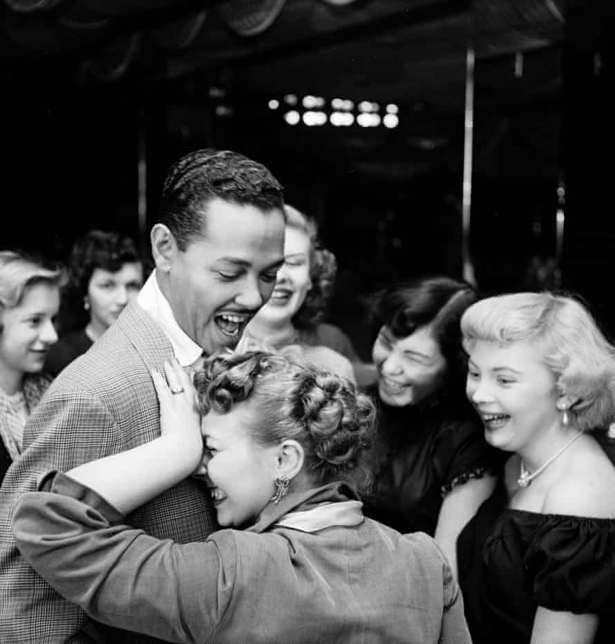 Singer Billy Eckstine gets a hug from an adoring fan after his show at Bop City as others look on. Photograph by Martha Holmes, Life, April 1950.