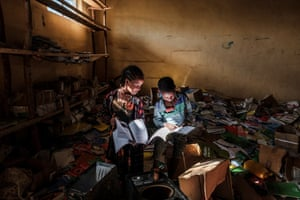 Two youngsters in the library of a primary school, damaged during fighting in the Tigray region