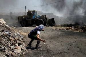 <strong>Kofr Qadom, West Bank </strong>Palestinian protester hurls stones at Israeli army bulldozer during clashes following a protest against Israeli settlements in Qadomem.