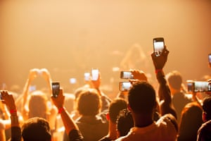 Fans using smartphones at a concert.