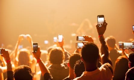People hold up phones at a concert