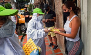 People receive bingo ballots in a game promoted by the city administration in Medellin, Colombia to encourage people to stay home during a new lockdown.
