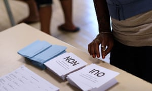A voter looks at ballot papers as people arrive to vote in the referendum on New Caledonia's independence from France.