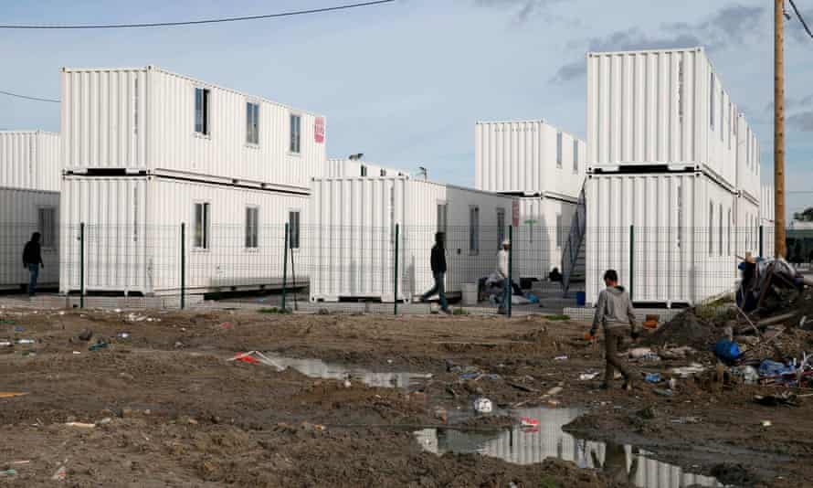 Refugees near containers used as temporary housing in the camp.