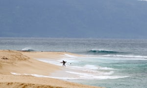 A surfer walks out of the ocean on Oahu's north shore near Haleiwa. Encouraging people to stay away has severely damaged Hawaii's economy, which relies heavily on the tourist dollar.