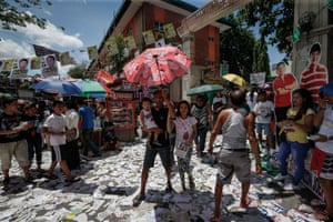 Manila, Philippines: Passersby walk through election litter surrounding a a polling station