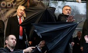 Security personnel use umbrellas to protect Miloš Zeman from missiles thrown by protesters during a speech in 2014