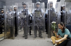 A female protester holds flowers as she sits in front of policemen in anti-riot gear outside the Legislative Council in Hong Kong.