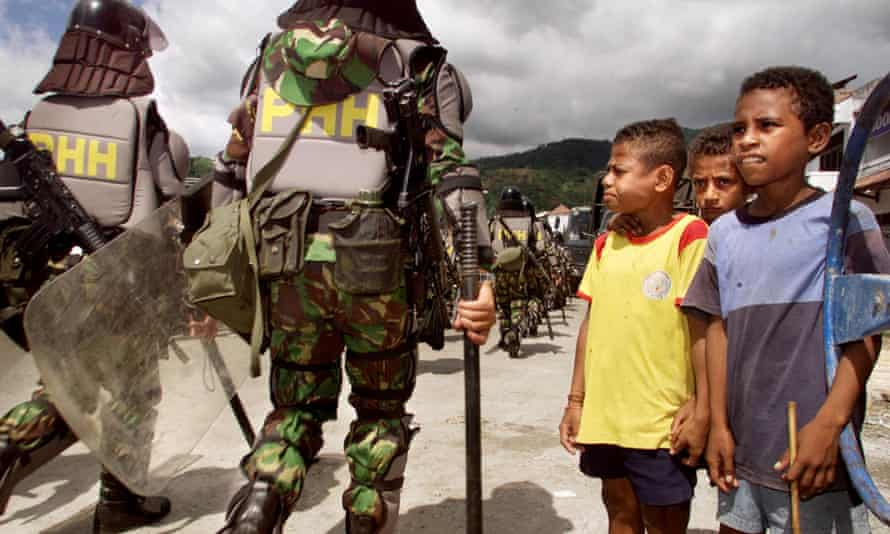 West Papuan boys, right, watch as Indonesian soldiers in full riot gear file past during a show of force in Jayapura, Irian Jaya, about 4,000 kilometers (2,400 miles) east of Jakarta Thursday, Nov. 30, 2000.