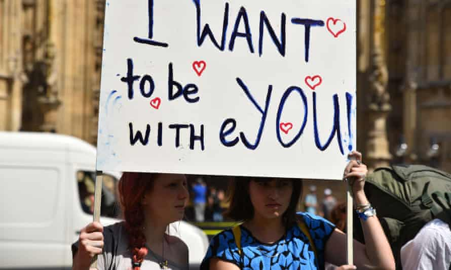 Students with placard reading 'I want to be with you'
