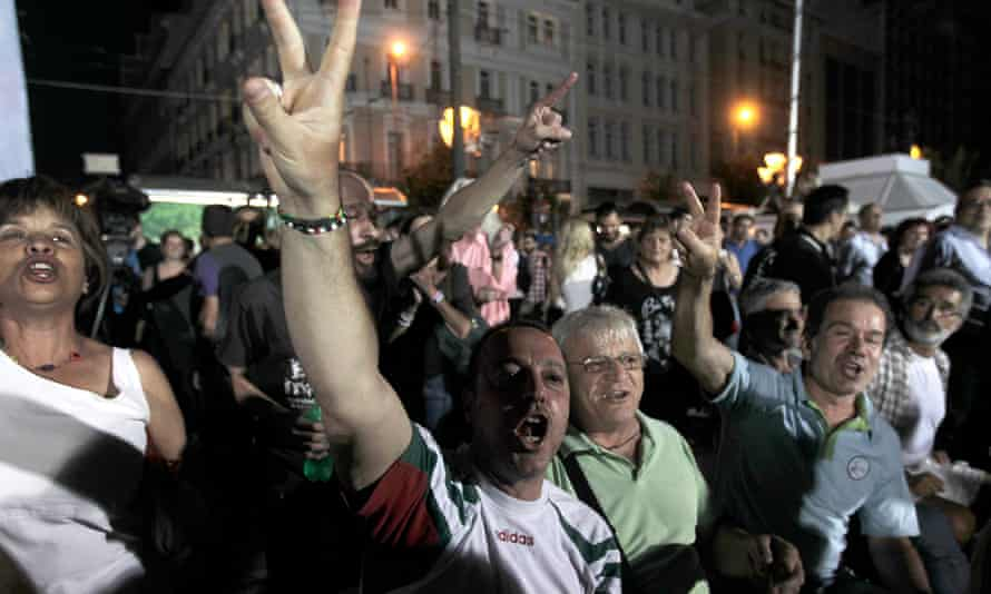 Supporters of the no campaign react after the first results of the referendum in Athens