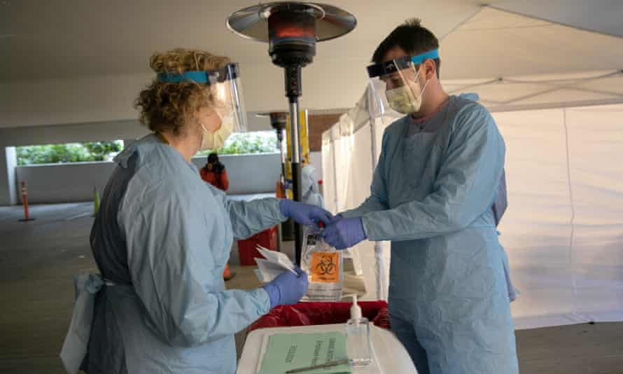 Nurses wearing protective clothing handle a bag with a potentially infected coronavirus swab at a drive-through testing center in Seattle, Washington.
