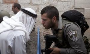 Israeli border policeman speaks to a Palestinian man near the scene of a stabbing in Jerusalem's Old City