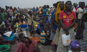 Families queue for aid at a settlement in Palorinya