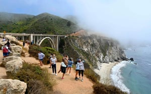 Tourists wearing masks enjoy the view of the Bixby Creek Bridge, on the Big Sur coast of California, on 1 August, 2020 amid the coronavirus outbreak.
