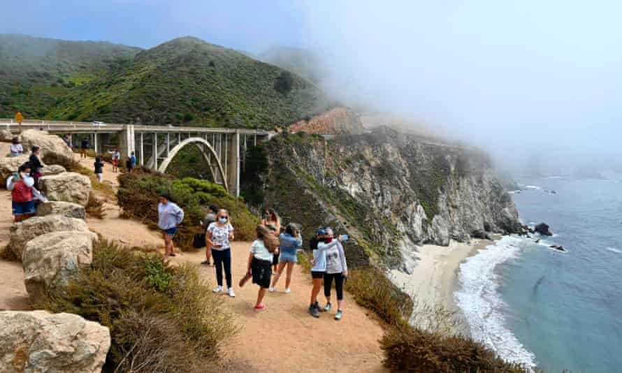 Tourists wearing masks enjoy the view of the Bixby Creek Bridge, on the Big Sur coast of California, on 1 August 2020 amid the coronavirus outbreak in the United States.
