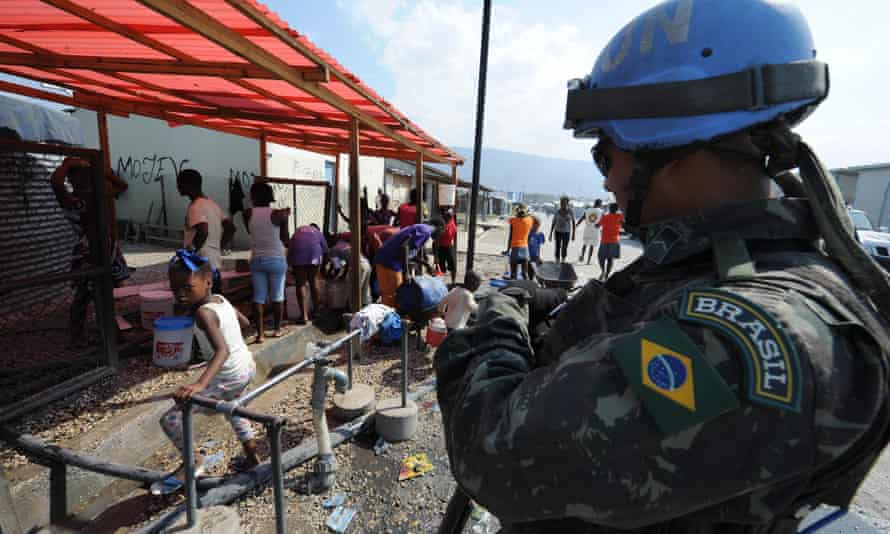 A Brazilian soldier stands guard at a water post in a camp for survivors of the January 2010 quake in Haiti