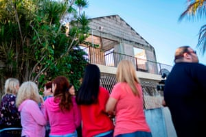 People in Ponce in front of a house where a man was killed when a wall fell on him