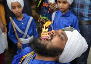A member of the Nihang, the Sikh warrior order, holds a flaming cube on his tongue during a procession marking the 413th anniversary of the installation of the Guru Granth Sahib at the Golden Temple, Amritsar, India