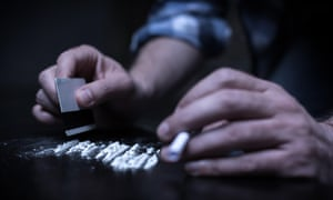 A person chopping lines of cocaine.