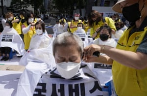 Workers in Seoul, South Korea, have their heads shaved as part of a protest demanding job security