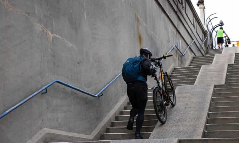 A cyclist is forced to push their bike up the ramp.