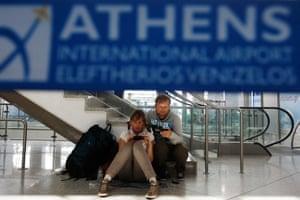 Passengers sit inside the Athens' Eleftherios Venizelos airpor.
