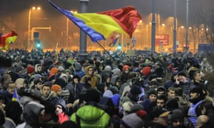 Crowds wave Romanian flags outside the government headquarters during a protest in Bucharest