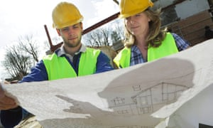 Male and female builders looking at plans on building site